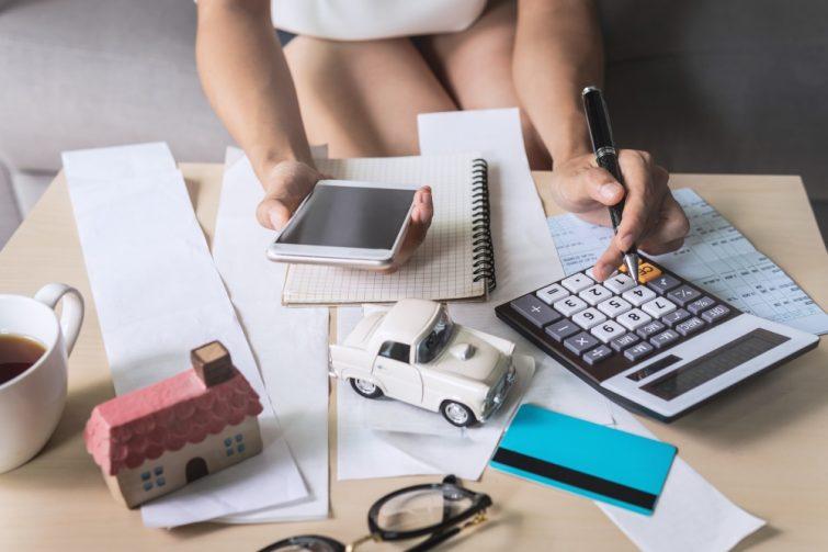 vrouw met rekenmachine rekent uit of zij recht heeft op verhuiskostenvergoeding